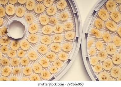 Top view of closeup homemade banana slices chips for drying dehydrating on dryer plates