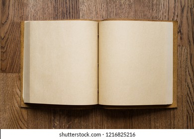 top view closeup of open book with leather covers and empty white pages on brown wooden parquet floor background