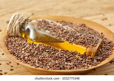 Top view closeup picture flax seeds and linseed oil in a glass bottle on a wooden background, shallow depth of field.