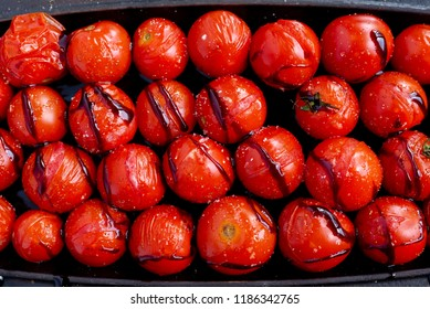 top view of a closeup of roasted cherry tomatoes in a black metal baking dish. The cherry tomatoes are roasted with extra virgin olive oil and balsamic vinegar