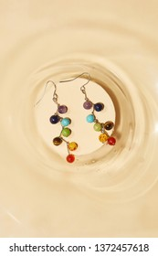 Top view closeup shot of long dangle earrings, adorned with multicolored stony pendants. The accessory set is isolated in middle of a round recess on the beige flat surface. Fashionable fashion item.