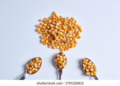 A top view closeup shot of a pile of corn kernels with three spoons also full of corn kernels