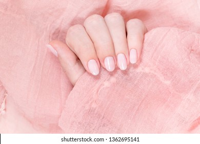 Top view closeup of two female hands isolated on pink cloth background. Fingernails with beautiful natural pink manicure. Horizontal color photography.
