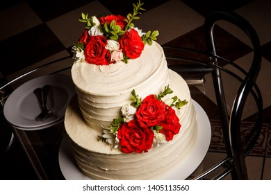top view closeup two-tiered cake with roses on glass tray