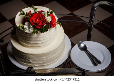top view closeup two-tiered cake on glass tray with plates and spoons