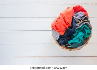 Top view Clothes in a laundry basket on Wood floor