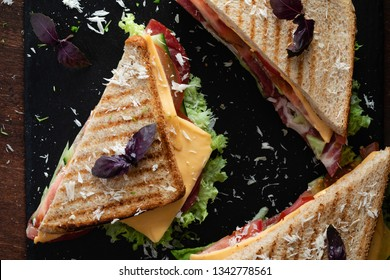 Top view of club sandwich on a dark table with ham, cheese, bacon and lettuce.