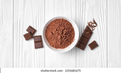 Top view of cocoa powder with broken chocolate bar as ingredient for confectionery on white wooden background