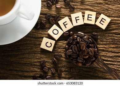 Top view of Coffee beans  lying in wooden spoons with wood texture background