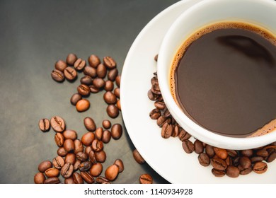 Top view of a coffee and coffee beans placed on the wooden table.