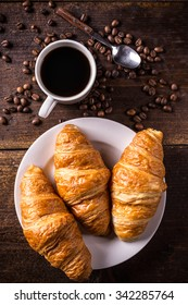 Top view of coffee and croissant with coffee bean