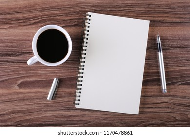 Top view of coffee cup and clear notepad with white pen on the office desk.