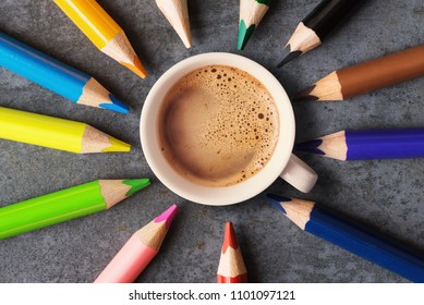 Top view of coffee cup and coloured pencils.