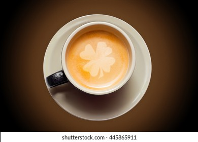 Top view of coffee cup with four leaf clover latte art on brown radial background.