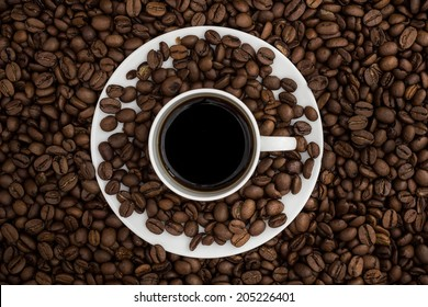 Top view of a coffee cup and a saucer filled with black coffee resting on coffee beans.