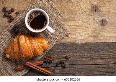 Top view of coffee and fresh croissant on old wooden table