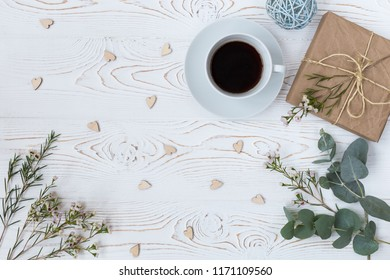 Top view of coffee, gift wrapped in kraft paper , hearts, flowers on white wooden table. Background with free space for text. Flat lay
