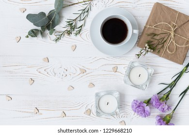 Top view of coffee, gifts wrapped in kraft paper , hearts, candles, flowers on white wooden table. Background with free space for text. Flat lay