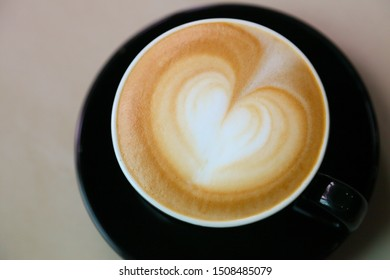 Top view of coffee latte art with heart pattern on top on rustic wooden table bar with copy space