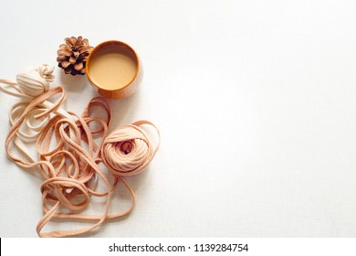 Top view of coffee and spruce cone and a tangle on the table.Coffee with milk and fir-cone and a unravel tangle on the white desk. Sunny day. Flat lay with copy space for text.