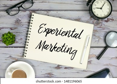 Top view of coffee,mobile phone,magnifying glass,clock,sunglasses,plant,pen and notebook written with Experiential Marketing on wooden background.