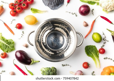 Top view of colander among uncooked vegetables isolated on white