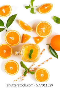 Top view of cold orange smoothie and orange fruits with green leaves isolated on white background.