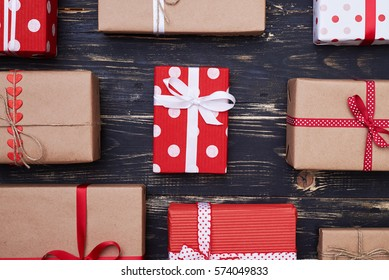 Top view of a collection of handmade presents wrapped in colorful paper tied with ribbon bows. View of nine gift present over grunge flat layout