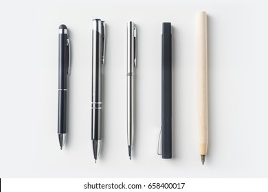 Top view of collection of pens on white background desk for mockup