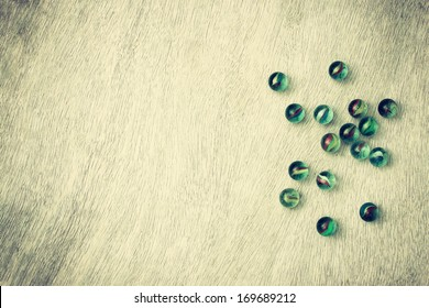 top view of collection of shiny marbles on wooden background. vintage effect.