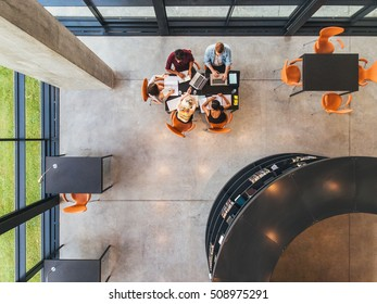 Top view of college students sitting in a library with books and laptop. Young people studying together at public library.
