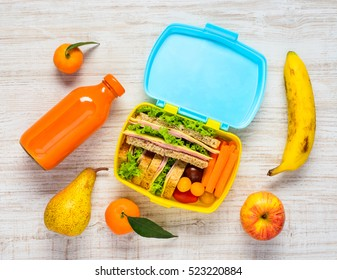 Top View of Colored Lunch Box with Drinks and Fruits
