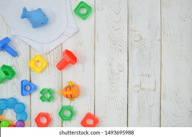 Top view colorful baby toys and building kit on white wooden background. Flat lay frame with copy space