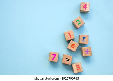 Top view of colorful bricks on turquoise wooden table background. Figures and arithmetic signs. Education concept