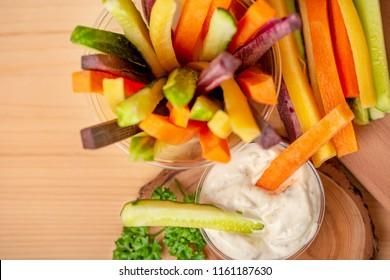 top view of colorful carrots, cucumbers vegetables julienned with mayonnaise on wooden board, concept of raw food snack