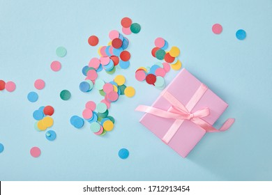 top view of colorful confetti near pink present on blue background