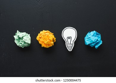 top view of colorful crumpled paper balls and light bulb drawing on black background, ideas concept