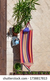 Top view of colorful hammock outdoor on terrace with cup of coffee, book and blanket ready for relaxing and enjoying vacation. Concept  little pleasures, self care, free time with favorite book