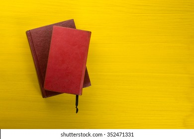 Top view of colorful hardback books on yellow background. Composition with vintage old hardback books, diary, fanned pages on wooden deck table. Books stacking. Back to school. Copy Space.