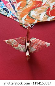 Top view of a colorful Japanese origami paper crane on a bright red texture with a stack of patterned origami papers in the background.