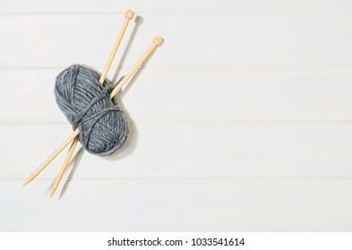 Top view of colorful knitting yarn balls and needlework accessories on white wooden textured table background. Photograph taken from above with copy space around products