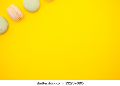 Top view of colorful macaron or macaroon on yellow background. Sweet snack