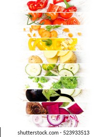Top view of colorful mix stripes with cut vegetables on white wooden desk; healthy eating concept; rainbow colors; white space for text