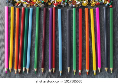 Top view of colorful pencil row on wooden desktop. Art and imagination concept