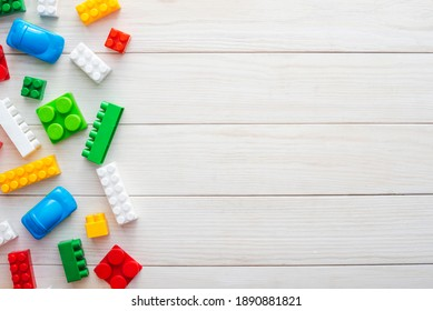 Top view of colorful plastic toy bricks on a white wooden background. Baby kids toys background.