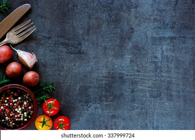 Top view of colorful spices and fresh vegetables for cooking on dark metal background with space for text. Bio Healthy food ingredients.