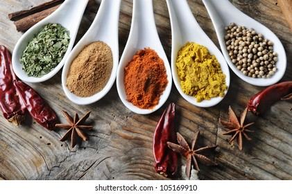 Top view of colorful spices on rustic wooden table with copyspace. Cooking and culinary concept.
