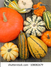 Top view of colorful squash and pumpkins on a rustic wooden surface