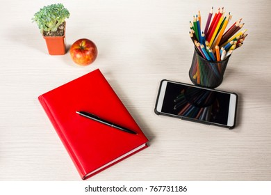 top view colorful stationery for business, creativity and study. red notepad, colored pencils, smartphone, apple, flower and bright office binders