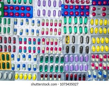 Top view of colorful tablets and capsule pills in blister packaging arrange with beautiful pattern. Pharmaceutical industry concept. Full frame pills background. Global pharmaceuticals